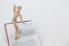 Ξύλινο ειδώλιο που στέκεται σε ένα ανοικτό βιβλίο Στοκ Εικόνα