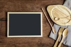 Ξύλινο εργαλείο στην κουζίνα στο παλαιό ξύλινο υπόβαθρο με το blackboa Στοκ Φωτογραφία