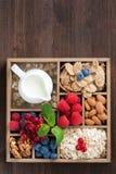 Ξύλινο κιβώτιο με τα στοιχεία προγευμάτων - oatmeal, granola, καρύδια, μούρο Στοκ Εικόνες