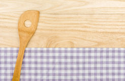 Ξύλινο κουτάλι σε ένα πορφυρό ελεγμένο επιτραπέζιο ύφασμα Στοκ φωτογραφίες με δικαίωμα ελεύθερης χρήσης