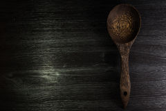 Ξύλινο κουτάλι στο μαύρο ξύλινο υπόβαθρο σύστασης Στοκ Εικόνα
