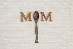 Ξύλινο κουτάλι τσαγιού με το ξύλινο κείμενο mom στο υπόβαθρο σύστασης καμβά Στοκ φωτογραφία με δικαίωμα ελεύθερης χρήσης