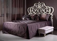Ξύλινο κρεβάτι πολυτέλειας στο δωμάτιο Στοκ φωτογραφία με δικαίωμα ελεύθερης χρήσης