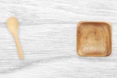 Ξύλινο κύπελλο και ξύλινο κουτάλι στον άσπρο ξύλινο πίνακα με το διάστημα κειμένων Στοκ εικόνα με δικαίωμα ελεύθερης χρήσης