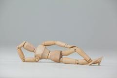Ξύλινο ξάπλωμα ειδωλίων στο πάτωμα με το χέρι στο κεφάλι Στοκ εικόνες με δικαίωμα ελεύθερης χρήσης