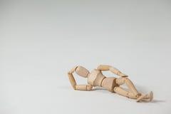 Ξύλινο ξάπλωμα ειδωλίων στο πάτωμα με το χέρι στο κεφάλι Στοκ φωτογραφίες με δικαίωμα ελεύθερης χρήσης