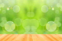 Ξύλινο πάτωμα και αφηρημένο πράσινο υπόβαθρο bokeh Στοκ Εικόνες