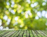 Ξύλινο πάτωμα και πράσινο δασικό υπόβαθρο θαμπάδων bokeh Στοκ εικόνα με δικαίωμα ελεύθερης χρήσης