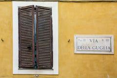 Ξύλινο παράθυρο με τα κλειστά παραθυρόφυλλα, το άσπρο ευρύ πλαίσιο και ένα όνομα Στοκ φωτογραφίες με δικαίωμα ελεύθερης χρήσης
