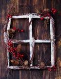 Ξύλινο παράθυρο πλαισίων με τα κόκκινα μούρα, το υπόβαθρο καλής χρονιάς κραταίγου, χιονιού και Χριστουγέννων κώνων Στοκ Φωτογραφίες