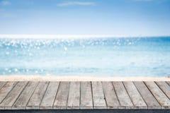 Ξύλινο πεζούλι με την παραλία άμμου και την τροπική θάλασσα στοκ φωτογραφία