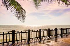 Ξύλινο πεζούλι στην παραλία που κοιτάζει στη λαμπιρίζοντας θάλασσα, κύματα, Στοκ Φωτογραφίες