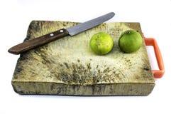 Ξύλινο πιάτο για το κομμένο συστατικό, το ξεφλουδίζοντας μαχαίρι και το φρέσκο ασβέστη Στοκ Εικόνα