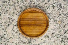 Ξύλινο πιατάκι στην πέτρα γρανίτη στοκ εικόνες