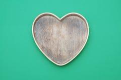 Ξύλινο πράσινο υπόβαθρο πιάτων καρδιών Στοκ φωτογραφία με δικαίωμα ελεύθερης χρήσης