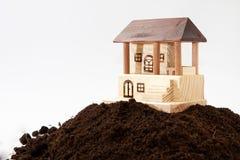 Ξύλινο πρότυπο σπιτιών στο σωρό του χώματος Στοκ Φωτογραφίες