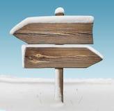 Ξύλινο σημάδι κατεύθυνσης με το λιγότερους χιόνι και τον ουρανό BG two_arrows-oppo στοκ εικόνες