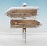 Ξύλινο σημάδι κατεύθυνσης με το χιόνι και τις χιονοπτώσεις BG two_arrows-oppo στοκ φωτογραφίες