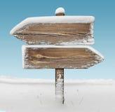 Ξύλινο σημάδι κατεύθυνσης με το χιόνι και τον ουρανό BG two_arrows-opposite_ στοκ εικόνα