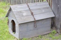 Ξύλινο σκυλόσπιτο με μια αλυσίδα σιδήρου και μια σπασμένη στέγη Στοκ εικόνα με δικαίωμα ελεύθερης χρήσης