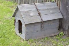 Ξύλινο σκυλόσπιτο με μια αλυσίδα σιδήρου και μια σπασμένη στέγη Στοκ Φωτογραφίες