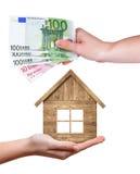 Ξύλινο σπίτι και ευρο- τραπεζογραμμάτια στα χέρια Στοκ Φωτογραφία