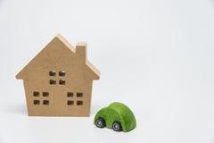 Ξύλινο σπίτι και πράσινο παιχνίδι αυτοκινήτων με το άσπρο υπόβαθρο και την εκλεκτική εστίαση Στοκ Εικόνες