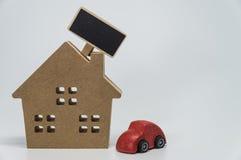 Ξύλινο σπίτι, κόκκινο παιχνίδι αυτοκινήτων και μικρός μαύρος πίνακας με το άσπρο υπόβαθρο και την εκλεκτική εστίαση Στοκ εικόνες με δικαίωμα ελεύθερης χρήσης