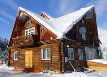 Ξύλινο σπίτι μια ηλιόλουστη χειμερινή ημέρα Στοκ Εικόνες