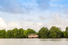 Ξύλινο σπίτι μόνο στο δάσος και τον ποταμό Στοκ Εικόνες