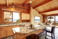 Ξύλινο σπίτι περιποίησης με το ανοικτό σχέδιο ορόφων Κουζίνα με την αντίθετη κορυφή γρανίτη Στοκ εικόνα με δικαίωμα ελεύθερης χρήσης
