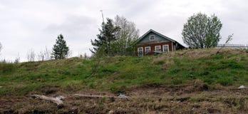 Ξύλινο σπίτι σε έναν λόφο από τον ποταμό στο βόρειο χωριό Pinega Στοκ Εικόνες