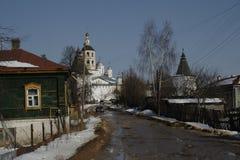 Ξύλινο σπίτι σε ένα υπόβαθρο ενός αρχαίου μοναστηριού Στοκ φωτογραφίες με δικαίωμα ελεύθερης χρήσης