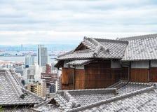 ξύλινο σπίτι της Ιαπωνίας με την αρχαία στέγη και εικονικές παραστάσεις πόλης και ουρανοξύστης Στοκ Εικόνα