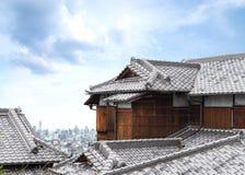 ξύλινο σπίτι της Ιαπωνίας με την αρχαία στέγη και εικονικές παραστάσεις πόλης και ουρανοξύστης Στοκ Φωτογραφίες