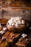 Ξύλινο σύνολο κύπελλων γλυκό popcorn στο ξύλινο εκλεκτής ποιότητας κύπελλο στον αγροτικό πίνακα κόκκινος τρύγος ύφους κρίνων απει Στοκ Εικόνες