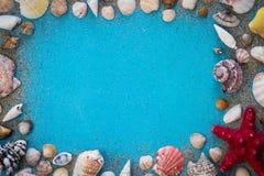 Ξύλινο τυρκουάζ υπόβαθρο με το πλαίσιο φιαγμένο από κοχύλια θάλασσας Στοκ Φωτογραφίες
