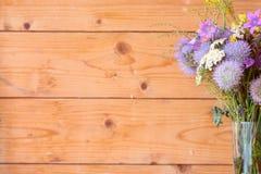 Ξύλινο υπόβαθρο, ανθοδέσμη των λουλουδιών στην εστίαση Στοκ Εικόνες