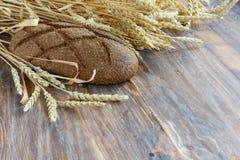 Ξύλινο υπόβαθρο με μια φραντζόλα του ψωμιού και τα αυτιά του σίτου Στοκ φωτογραφία με δικαίωμα ελεύθερης χρήσης