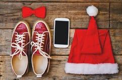 Ξύλινο υπόβαθρο με τα τηλεφωνικά πάνινα παπούτσια κόκκινη κουκούλα και ένα τόξο Στοκ Φωτογραφία