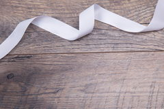 Ξύλινο υπόβαθρο με την άσπρη κορδέλλα Στοκ φωτογραφία με δικαίωμα ελεύθερης χρήσης