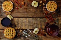 Ξύλινο υπόβαθρο με τις πίτες, το τσάι και τα καρύδια μήλων Στοκ Εικόνες