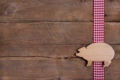 Ξύλινο υπόβαθρο με τον καλό χοίρο τύχης στην ελεγμένη κορδέλλα Στοκ Εικόνες