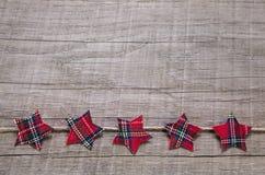 Ξύλινο υπόβαθρο που διακοσμείται με τα κόκκινα αστέρια Χριστουγέννων του υφάσματος Στοκ Φωτογραφία