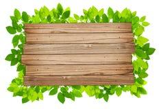 Ξύλινο υπόβαθρο σανίδων με τα πράσινα φύλλα στοκ εικόνες