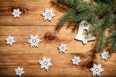Ξύλινο υπόβαθρο Χριστουγέννων με άσπρα ξύλινα snowflakes και τον κωνοφόρο κλάδο Στοκ εικόνα με δικαίωμα ελεύθερης χρήσης