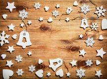 Ξύλινο υπόβαθρο Χριστουγέννων με άσπρα ξύλινα snowflakes, τα αστέρια και τα κουδούνια Στοκ Εικόνες