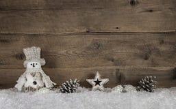 Ξύλινο υπόβαθρο Χριστουγέννων με έναν χιονάνθρωπο και ένα φυσικό decoratio Στοκ Φωτογραφίες
