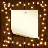 Ξύλινο υπόβαθρο Χριστουγέννων με τα φω'τα και το έγγραφο Στοκ Εικόνες
