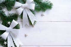 Ξύλινο υπόβαθρο Χριστουγέννων με τους κλάδους και το τόξο έλατου Στοκ Εικόνα